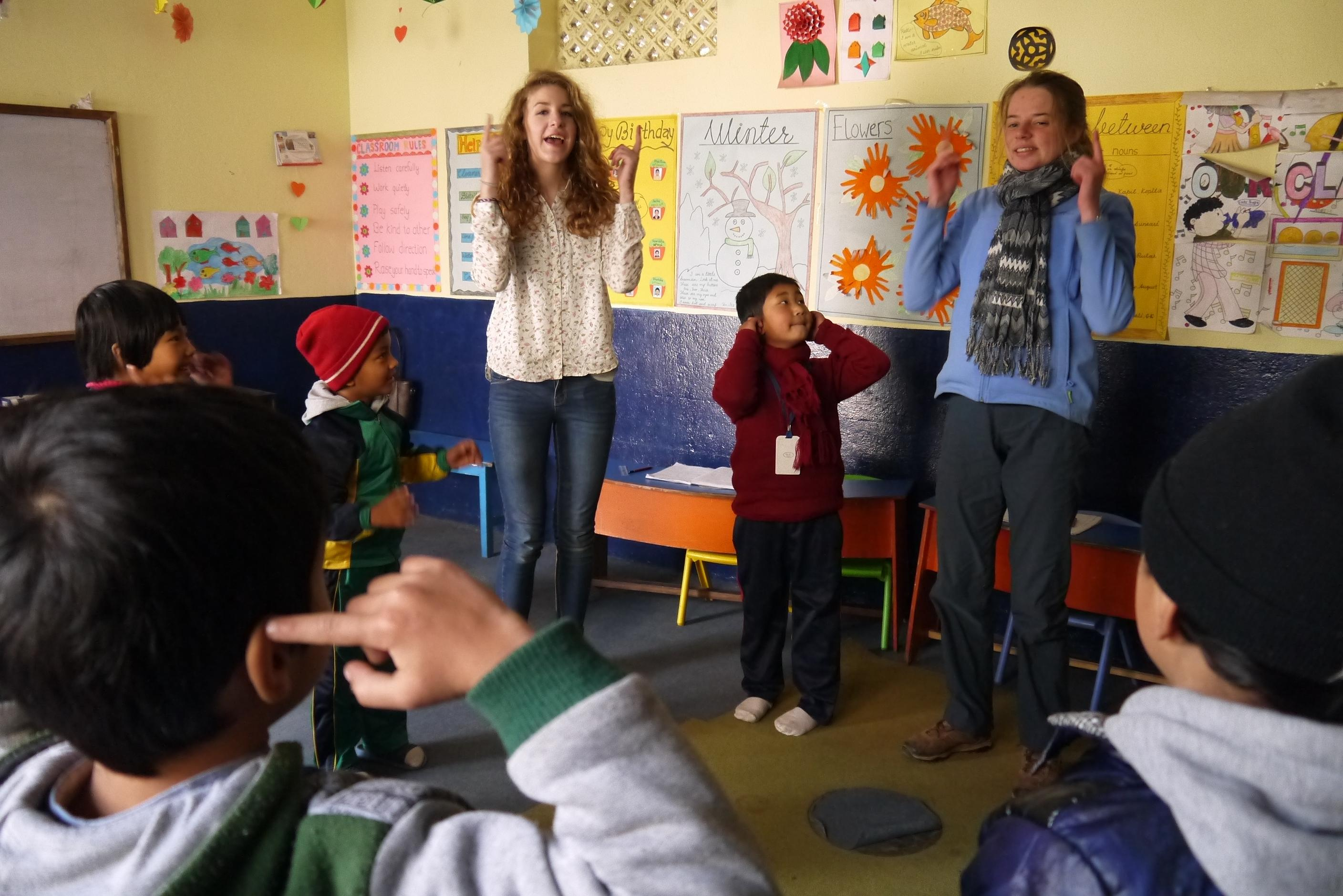 Female Childcare volunteer working with children in Nepal are leading physical activitie in a day care centre during a project.